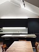 Blaugraue Designerküche mit Küchentheke, indirekter Beleuchtung und Edelholztisch im Dachgeschoss