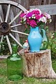 Blue enamel jug of Sweet William on tree stump