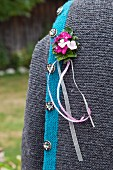 Buttonhole of Sweet William and ribbons pinned to traditional German cardigan