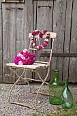 Bouquet and heart-shaped wrath of Sweet Williams on vintage folding chair in front of rustic barn door