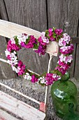 Heart-shaped wreath of Sweet Williams hung on backrest of vintage folding chair