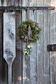 A wreath of pine cones, green twigs, moss and wooden stars with Japanese roses in a hanging vase against a weathered wooden door