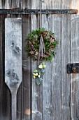 Kranz aus Zapfen, grünen Zweigen, Moos und Holzsternen mit Japanrosenblüten in Hängevasen an verwitterter Holztür