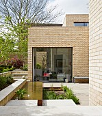 Geometric terrace with flowerbed and pool outside modern brick house