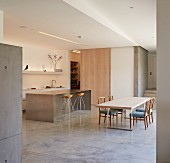 Open-plan designer kitchen with island counter, dining table and upholstered chairs in minimalist interior