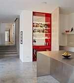 View across stainless steel kitchen counter to floor-to-ceiling home bar with swivelling door and red interior and into corridor with concrete steps