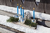 Advent arrangement of shiny baubles used as candle holders on snowy, weathered wooden surface
