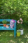 Crocheted cushions on blue-painted garden bench next to pink potted rose