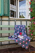 Crocheted blanket of hexagons in shades of blue and purple on vintage garden bench against rustic façade of house
