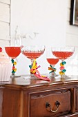 Various glasses with stems decorated with uninflated balloons