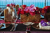 Table festively set with place settings and flower arrangements in gilt containers for Indian wedding