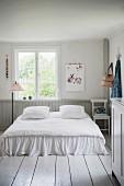 Romantisches Doppelbett auf weißem Dielenboden in ländlichem Schlafzimmer mit nostalgischem Flair