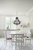 White table and wooden chairs below chandelier in rustic interior with white wooden floor