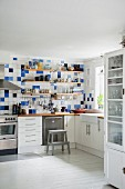 Shelves on blue and white wall tiles above kitchen counter on white base units in corner of kitchen