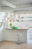 Bar stool at counter with white wood-clad base unit in open-plan kitchen
