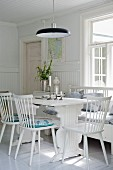 White wooden chairs and wooden table in dining area below black pendant lamps in Scandinavian interior