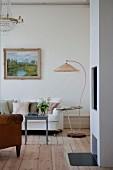Stehleuchte mit gebogenem Gestell und Ablage neben hellem Sofa und grauem Couchtisch im Wohnzimmer