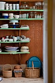 Crockery on shelves covered in green paper above various baskets on floor
