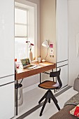 A wooden swivel office chair in front of a minimalistic desk by a window