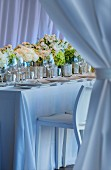 Wedding dinner table festively decorated with row of bouquets and place settings