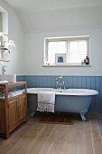 Free-standing, pale blue bathtub against matching, vintage-style blue wainscoting