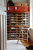 Haberdashery cabinet used as chest of drawers, step ladder and red storage boxes in dressing room