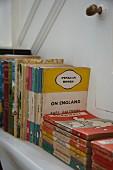 Vintage English books arranged stood and stacked on bookshelf