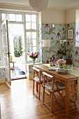 Dining room with pastel floral wallpaper, solid-wood dining table and view into vintage-style conservatory