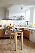 Simple fitted kitchen with wooden fronts, plain oak floor and narrow table in bright, country-house interior
