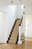 Restored wooden staircase painted white, brown and beige in white country-house foyer