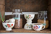 Vintage bowls and storage jars in rustic wine crate used as kitchen shelf