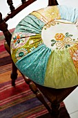 Turquoise and orange round patchwork cushion with embroidered panels on antique wooden chair