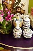 Kunsthandwerkliche traditionelle Vasen auf violetter Tischplatte mit Blumenschmuck