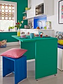 A small apartments with a green, space-saving breakfast table, a matching wall and a blue wooden stool