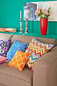 Colourful cushions on a sofa bed with storage space behind in an openable green shelf