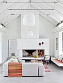 Exposed roof structure, pale grey corner couch, open fireplace and pendant lamps with white lampshades in white interior