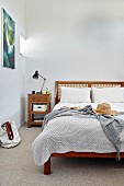 Double bed with headboard and vintage bedside table in bedroom