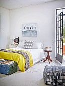 Schlafzimmer mit Doppelbett und gelber Tagesdecke, antikem Nachttisch und Sitzpouf mit gemustertem Bezug