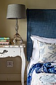 Table lamp with grey lampshade on vintage bedside table next to bed with headboard upholstered in blue fabric