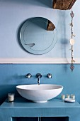 White countertop sink on light blue base unit against wall in same colour below round mirror with bird motif and decorative chain