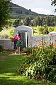 Frau und Kind vor Gartenmauer mit geöffneter Tür in sommerlichem Garten vor Hügellandschaft