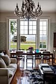 Sofa und Couchtisch vor Essplatz in elegantem Ambiente am Fenster mit Landschaftsblick
