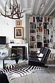 Wohnraum in eklektizistischem Stil, Sessel mit schwarzen Polstern und Klassiker Coffeetable auf Zebrafell vor Kamin