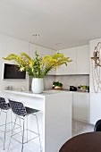 Vase of yellow flowers on white counter in fitted kitchen