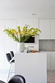 Gelber Blumenstrauss in Vase auf weisser Theke in Einbauküche