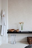 Wooden bowls and amaryllis buds on black floating shelf above transparent stool