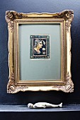 Antique picture in gilt frame above sculpture of supine figure