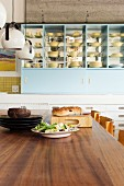 Yellow crockery on kitchen shelves seen across wooden dining table