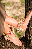 Woman's feet with red-painted toenails and flower anklets