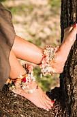Blumenschmuck an Frauenfüßen mit rotem Nagellack